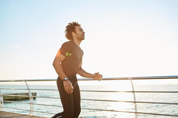 Loper in sportkleding doen cardiotraining op strand in de ochtend