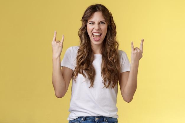 Los gaan. gedurfd geamuseerd knap europees meisje met krullen doet opgewonden opgewonden plezier geniet geweldig concert show ja rock-n-roll heavy metal gebaar grimassen tevreden