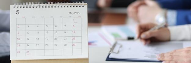 Losbladige papieren kalender staande op tafel tegen de achtergrond van mensen uit het bedrijfsleven close-up