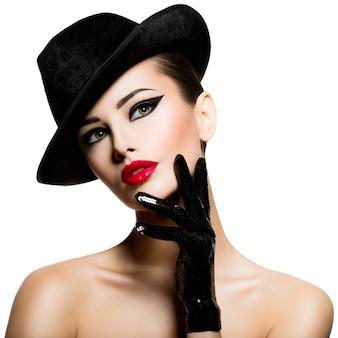 Сlose-up portret van een vrouw in een zwarte hoed en handschoenen met rode lippen poneren
