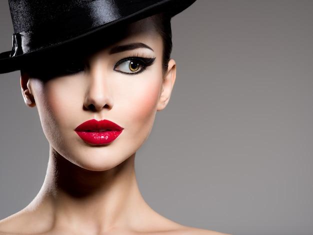 Сlose-up portret van een vrouw in een zwarte hoed met rode lippen poseren