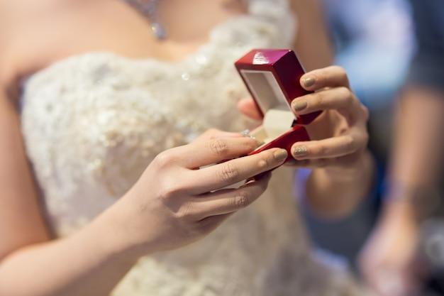 Loseupfoto van een bruid die een doos met gouden ringen houdt
