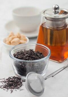 Losse biologische zwarte thee met zeef-infuser en helderglazen theepot met rietsuiker en witte keramische kop op lichte tafelachtergrond.