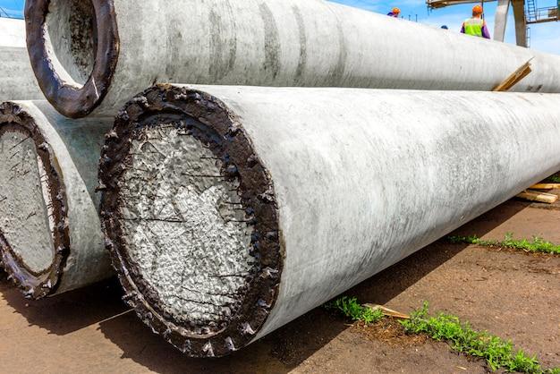 Lossen van betonnen hoogspanningsmasten op de bouwplaats met behulp van een hijskraan. voorbereiding voor installatie van hoogspanningslijnen
