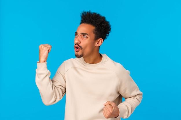 Loterij, sportweddenschap, mensen concept. gespannen en opgewonden jonge knappe afro-amerikaanse man kijkt naar een wedstrijd op tv in de pub, kijkt naar het linkerscherm, vuistpomp wortelt voor het team, zegeviert, blauwe muur
