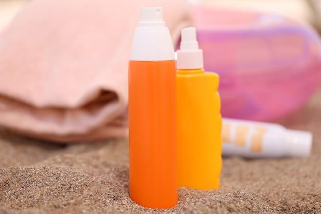 Lotion en zonnebrandcrème staan op zand op het strand