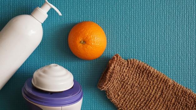 Lotion, sinaasappel, douchespons en anti-cellulitis stimulator op een blauwe achtergrond. gezond en mooi huidconcept.