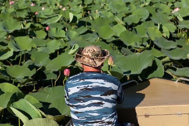 Lotus bloem plantage. man in boot bestudeert, observeert en fotografeert bloemknop.