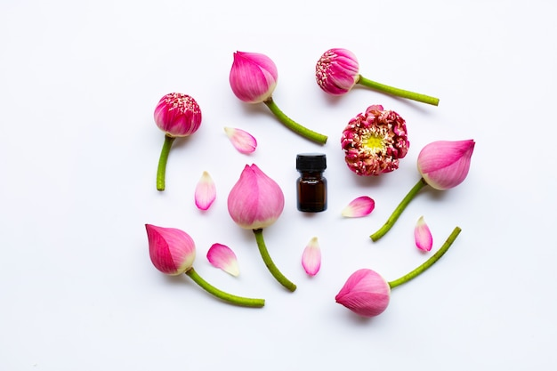 Lotus-essentiële olie met lotusbloembloemen op wit.