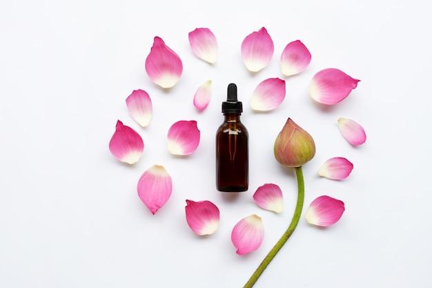 Lotus-etherische olie met lotusbloembloemen op witte achtergrond.