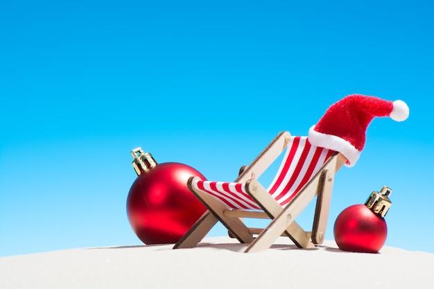 Lounge stoel met kerstmuts en kerstballen op het strand