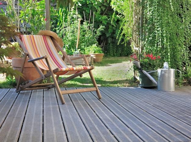 Lounge stoel op houten terras in een tuin