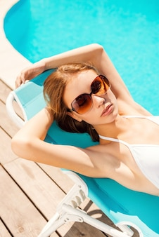 Loungen bij het zwembad. bovenaanzicht van mooie jonge vrouw in witte bikini ontspannen in de ligstoel bij het zwembad