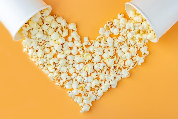 Love films concept. de popcorn in document vakje verspreidde zich op oranje hart gevormde hoogste mening als achtergrond, exemplaarruimte voor tekst. cinema snack concept. popcorndoos mocap