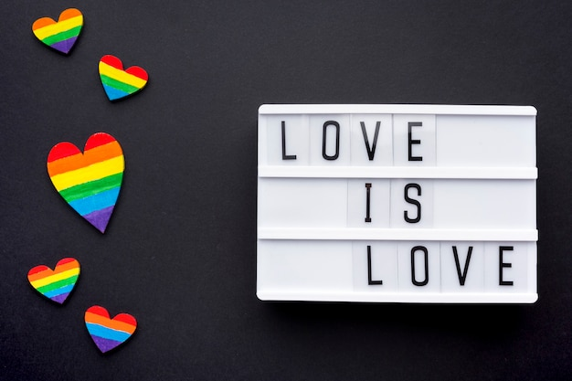 Love is love pride quote with rainbow hearts