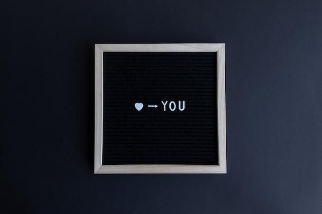 Love you quote op een bord met een houten frame op een kleurrijke achtergrond