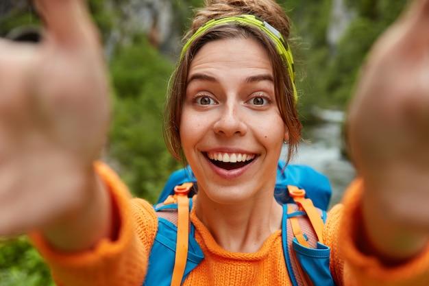 Lovey blij vrouwelijke toerist maakt selfie portret, kijkt camera gelukkig, staat met rugzak tegen groene natuurruimte