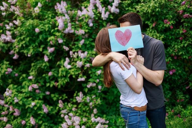 Loving young couple houd een kaart met rood hart buitenshuis. liefdesverhaal concept. romantisch moment buiten
