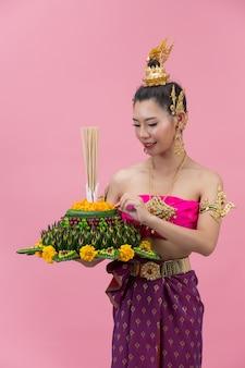 Loy krathong festival; vrouw in thaise traditionele outfit met versierde drijfvermogen