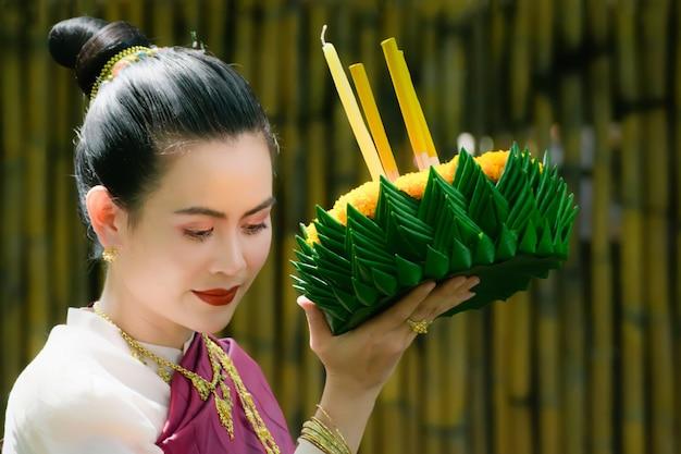 Loy krathong traditioneel festival van thailand. de vrouw van azië in thaise kledings traditionele holding kratong.