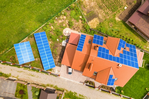 Lucht bovenaanzicht van nieuw modern woonhuisplattelandshuisje met het blauwe glanzende systeem van foto voltaic panelen op dak. hernieuwbaar ecologisch groen energieproductieconcept.