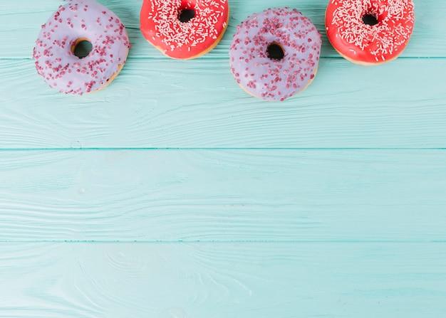 Lucht bovenaanzicht verse die donuts op een rij op houten lijst wordt geschikt