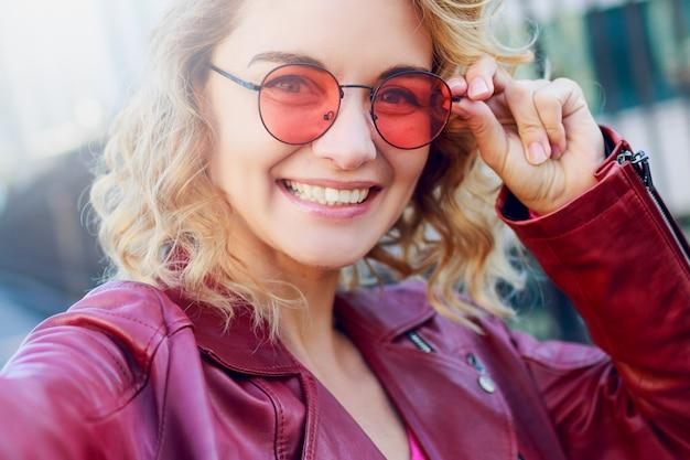 Lucht charmante vrouw die zelfportret maakt. krullend blond kapsel. roze bril en herfst trendy leren jas.