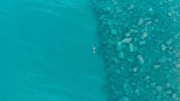 Lucht: een persoon duiker zwemmen vissen in kristalheldere middellandse zee, diepblauwe transparant water, zomersport vakantie concept