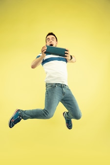 Lucht geluid. volledig lengteportret van gelukkige springende mens met gadgets op geel.