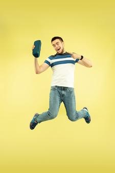 Lucht geluid. volledig lengteportret van gelukkige springende mens met gadgets op gele achtergrond. moderne technologie, concept van vrijheid van keuzes, concept van emoties. gebruik een draagbare luidspreker als een superheld tijdens de vlucht.