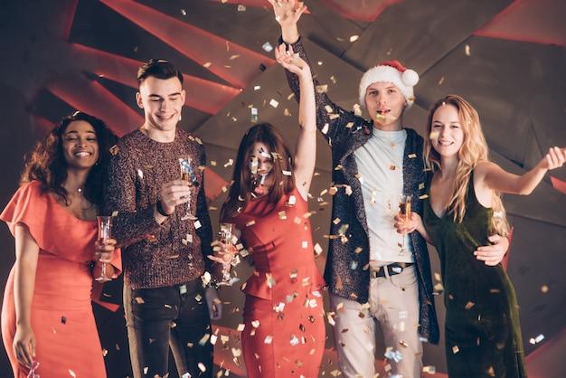 Lucht in de confetti. vijf goede vrienden in goede kleding zijn op het feest van het nieuwe jaar