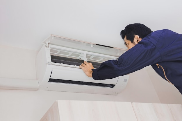 Lucht monteur reparateur in blauwe uniform controleert de airconditioner