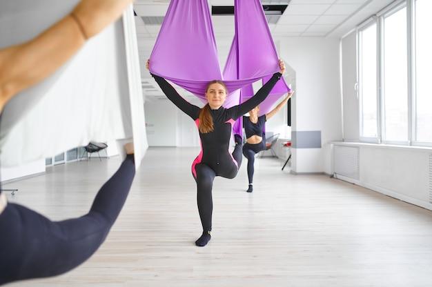 Lucht- of antizwaartekrachtyoga, groepstraining, hangmatten. een mix van fitness, pilates en dansoefeningen. vrouwen op yogi-training in de sportschool, fit levensstijl