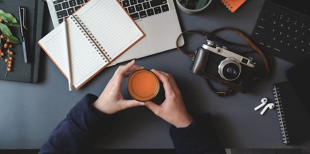 Lucht schot van jonge vrouw die een glas jus d'orange houdt terwijl het werken van haar project