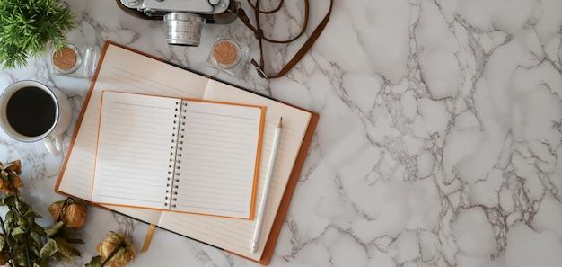 Lucht schot van moderne werkplaats met open notitieboekje en bureaulevering op marmeren bureau met exemplaarruimte