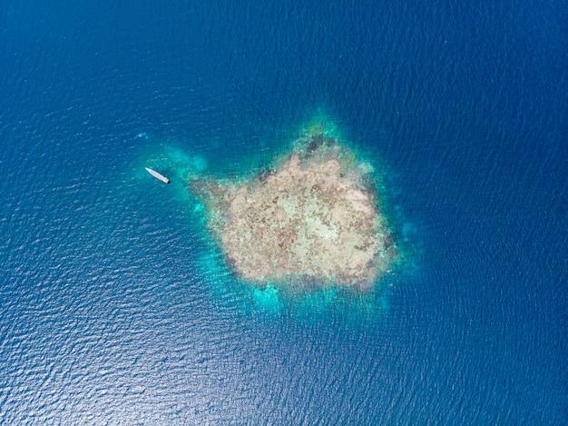 Lucht top-down mensen die op koraalrif tropische caraïbische overzees, turkoois blauw water snorkelen. de archipel van indonesië wakatobi, marien nationaal park, toerist duikt reisbestemming