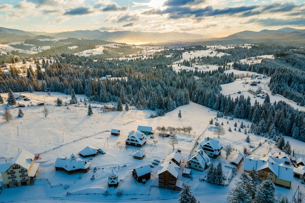 Lucht winterlandschap met kleine dorpshuizen tussen besneeuwde bossen in koude bergen in de avond.