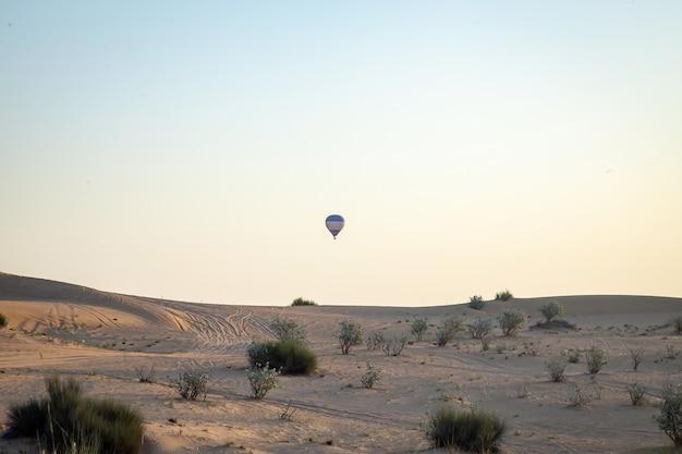 Luchtballon die over zandduinen vliegt met heldere blauwe lucht
