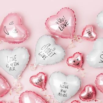Luchtballonnen van hartvormige folie op pastelroze ondergrond. liefdesconcept. vakantie vieren. valentijnsdag of bruiloft/vrijgezellenfeest decoratie. metalen ballon