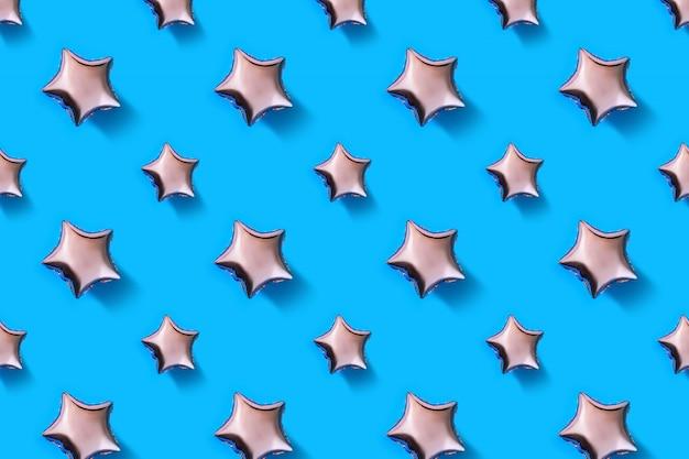 Luchtballonnen van stervormige folie op pastelblauw patroon