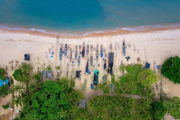 Luchtfoto afbeelding van zee, strand, jungle en houten boot met blauwe hemel in nakhon si thammarat, thailand