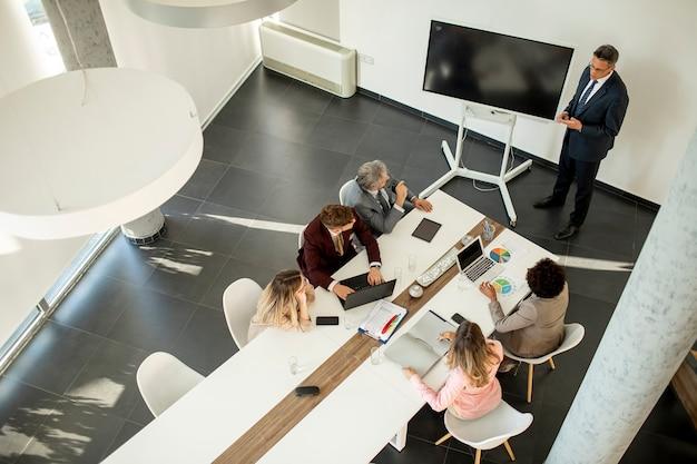 Luchtfoto bij een groep zakenmensen die samenwerken en een nieuw project voorbereiden op een vergadering op kantoor