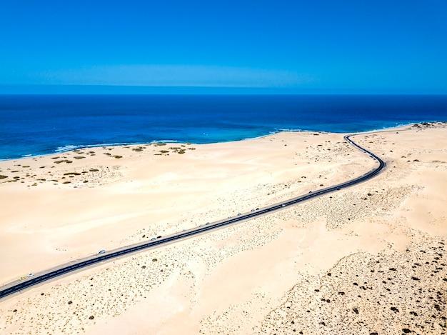 Luchtfoto boven weergave van geel tropisch zandstrand met zwarte lange weg en auto reizen - oceaan blauwe golven en kust - zonsondergang tijd met lange mooie schaduw - concept van zomervakantie