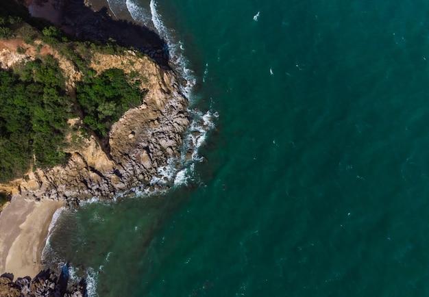 Luchtfoto bovenaanzicht eilandrots en kuif in de prachtige groene zee