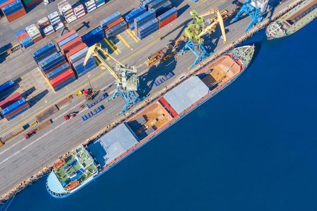 Luchtfoto bovenaanzicht enorm vrachtschip afgemeerd aan de pier in de haven