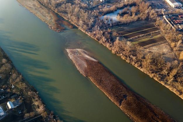 Luchtfoto bovenaanzicht, platteland panorama van klein eiland met droog gras in een rustige rivier op zonnige dag. drone fotografie.