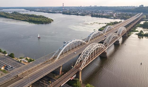 Luchtfoto bovenaanzicht van auto- en spoorweg darnitsky brug over de rivier de dnjepr. de horizon van de de stadszonsondergang van kiev, de oekraïne