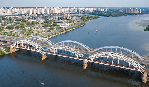 Luchtfoto bovenaanzicht van auto- en spoorweg darnitsky brug over de rivier de dnjepr. de skyline van de stad kiev, oekraïne