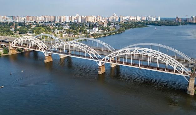 Luchtfoto bovenaanzicht van auto- en spoorweg darnitsky brug over de rivier de dnjepr