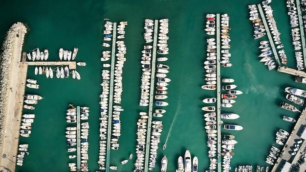 Luchtfoto bovenaanzicht van boten en jachten in gedokt in zeehaven bij zonsondergang. marien parkeren van moderne motorboten